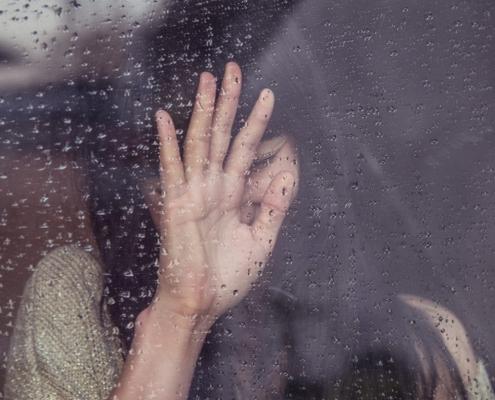 thema trennungsberatung -eine frau am fenster es regnet sie hält sich die hand vor gesicht