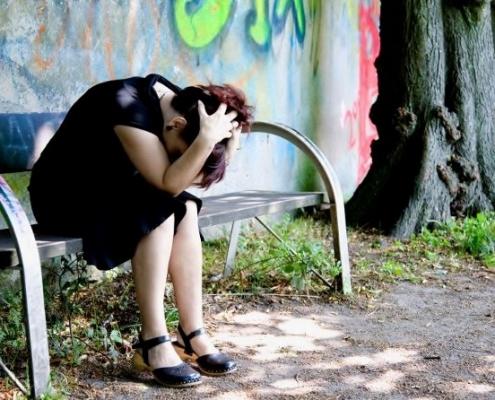 burnout -eine frau sitz auf einer bank sie ist sehr verzweifelt-thema - psychologische beratung krisen bewältigung